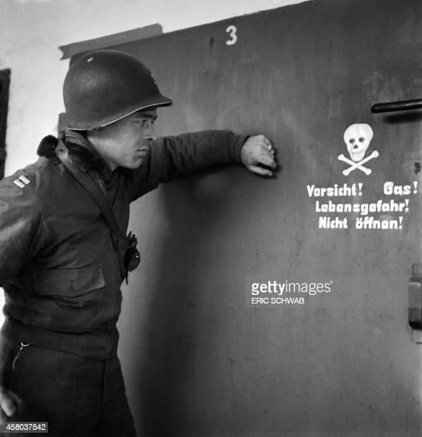 A US soldier is seen in front of the door of a gas chamber at the Nazi concentration camp of Dachau in late April or early May 1945 after the camp...