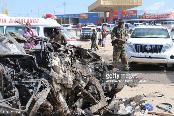TOPSHOT A soldier is seen next to the wreckage of car that was damaged during the car bomb that exploded in Mogadishu that killed more than 20 people...