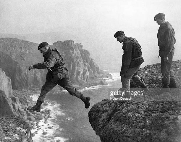 A soldier jumps across a gap in two cliffs as Royal Marine Commandos participate in rigorous training at the Royal Marine Commandos School in...