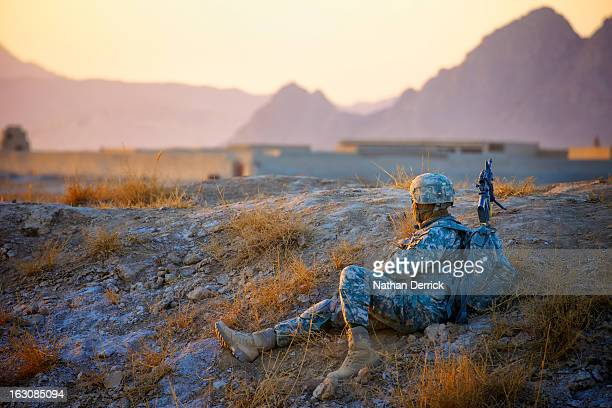 Soldier keeps an eye out as the sun sets during a patrol in Kandahar, Afghanistan. Most of the time spent on a deployment is characterized by...