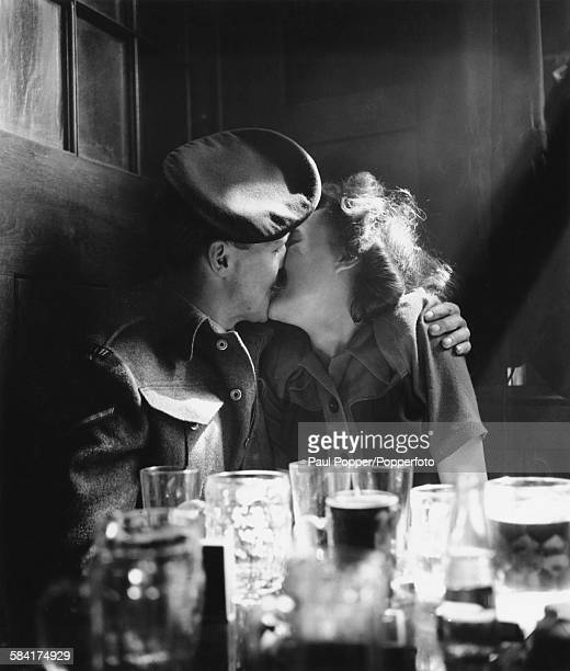 A soldier kissing a young woman in a pub during VE Day celebrations in London 8th May 1945