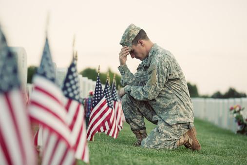 Soldier kneeling at grave 155598789