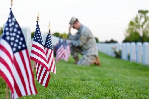 Soldier kneeling at grave 173198761