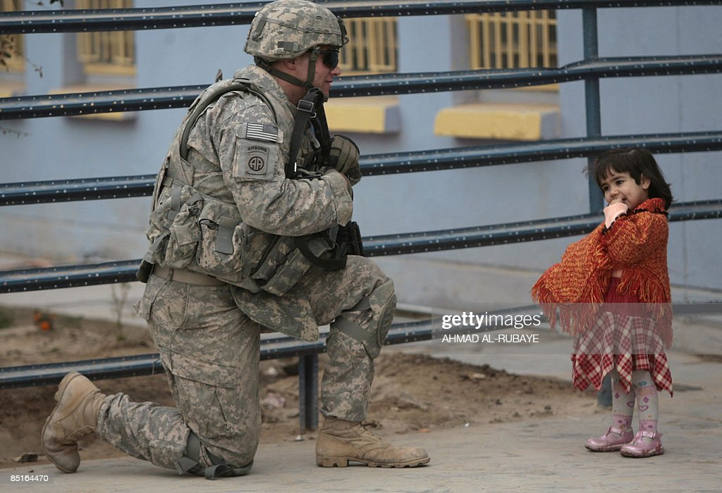 A US soldier kneels as he speaks to a li : News Photo