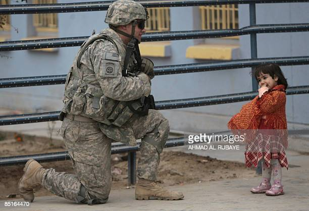 A US soldier kneels as he speaks to a little Iraqi girl as he and other secure the area along with Iraqi soldiers for the arrival of a shipment of...