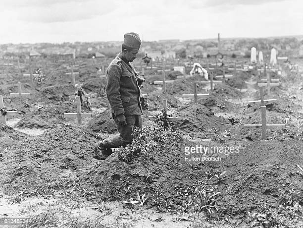 Soldier kneels at the graveside of a fellow Serbian in a huge field dedicated to the Serbs who were killed during an Austrian bombardment in 1915.