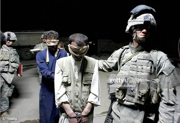 US soldier leads suspected insurgents that were arrested during a night patrol in the town of Tal Afar 01 April 2006 A US helicopter crashed...