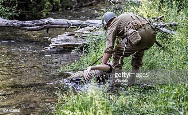 soldier lifting wounded wwii us army combat casualty - fallen soldier stock pictures, royalty-free photos & images