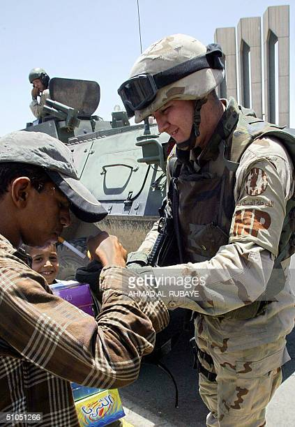 US soldier lights the cigarette of an Iraqi man while patrolling central Baghdad 12 July 2004 Five roadside bombs exploded in central Baghdad as a US...