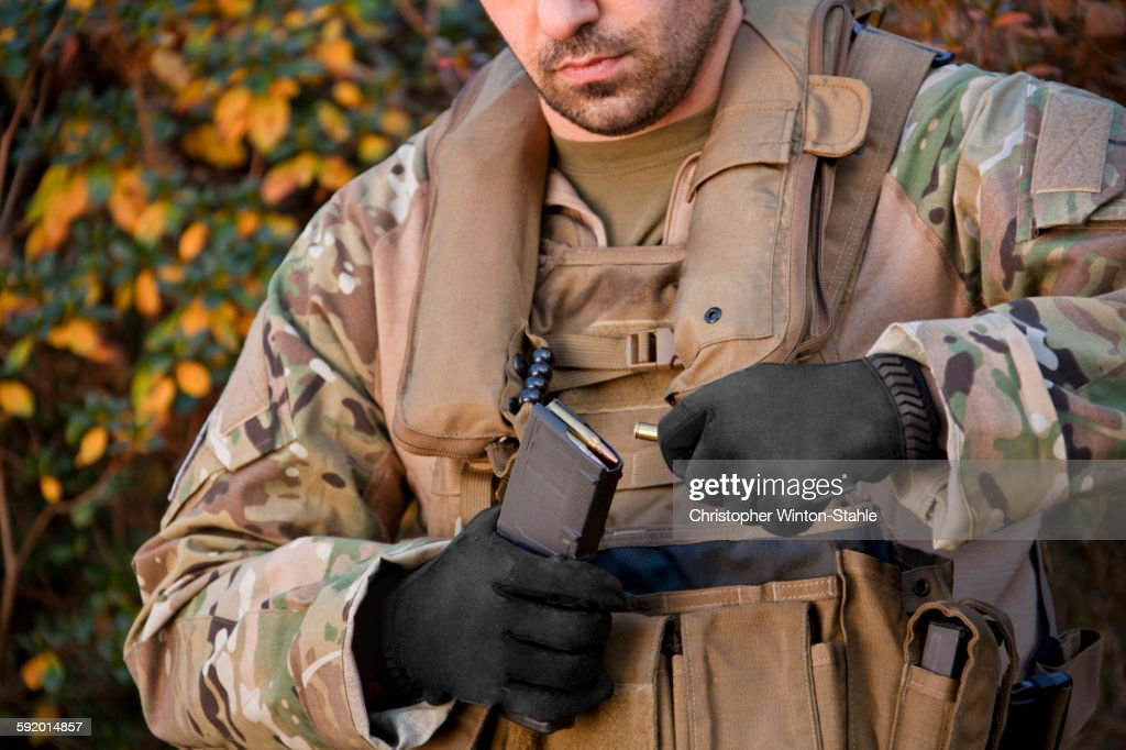Soldier loading automatic weapon during training : Stock Photo