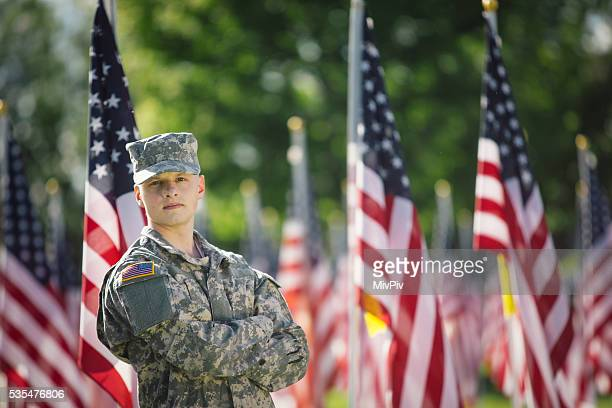 Soldier looking over his shoulder in fornt of American flags