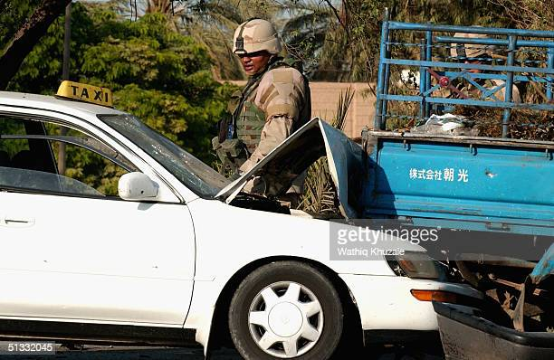 S soldier looks at a damaged civilian car at the scene of a car bomb explosion September 21 2004 in Baghdad Iraq A car bomb exploded near a US...