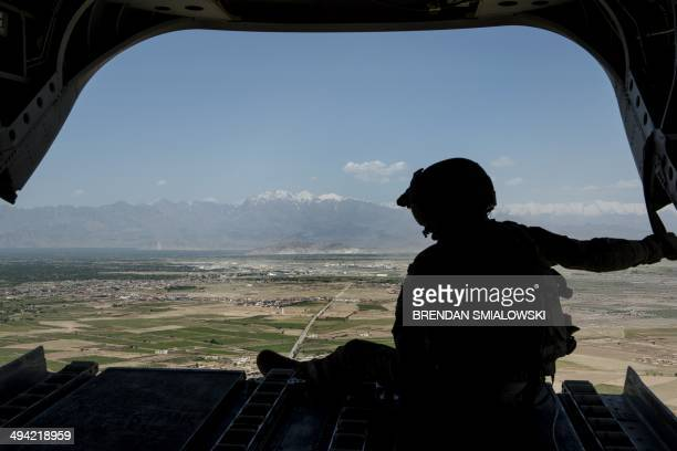 A US soldier looks at a mountain range in Afghanistan's Logar Province from a US Chinook helicopter on May 28 2014 US forces will complete their...