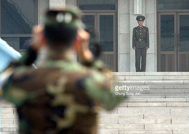 S soldier looks at a North Korean soldier at the border village of Panmunjom June 18 2003 north of Seoul South Korea North Korea vowed to strengthen...