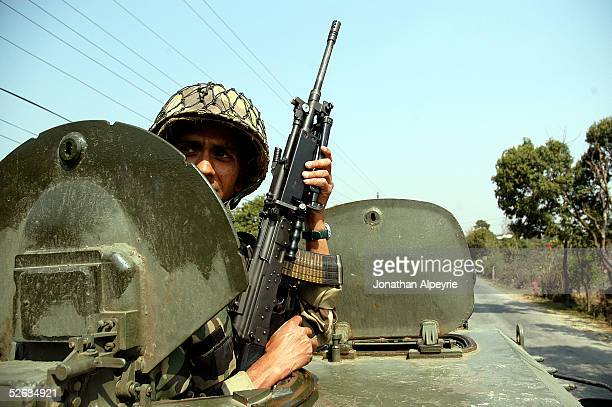 A soldier looks for Maoists hiding near the road March 1 2005 in the eastern Terai district of Hetauda Nepal All the equipment the soldiers use...