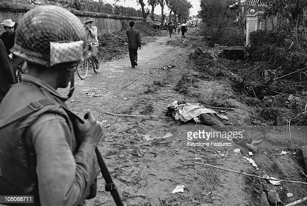 A US soldier looks on as refugees pass a corpse in a street after the Battle of Hue during the Vietnam War 1968