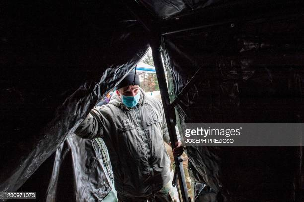 Soldier looks through a tent flap as it is put up at a vaccination center in Londonderry, New Hampshire on February 4, 2021. - The drive-through...