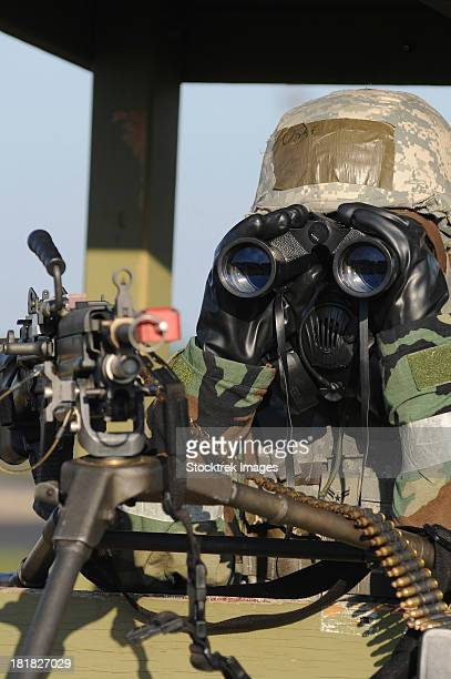 A soldier looks through binoculars from his outpost during an Operational Readiness Exercise.