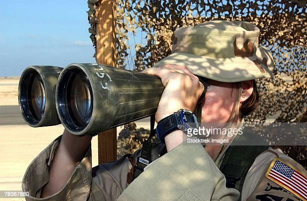 A soldier looks through binoculars.
