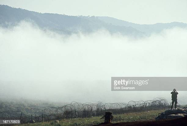 Soldier looks through the mist while on patrol at a US Marine base, Khe Sanh, South Vietnam, 1968.
