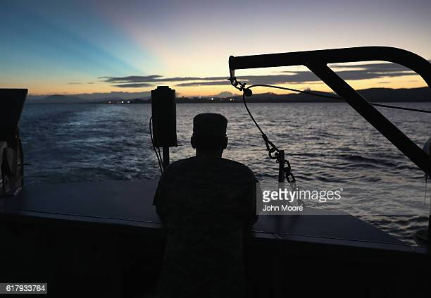 A US soldier looks towards the first rays of sunlight while on a dawn ferry near the military prison known as Gitmo on October 24 2016 at at the US...