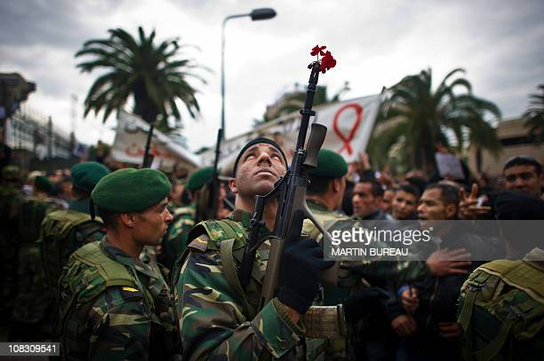 A soldier looks up as he holds a gun during a demonstration against Ben Ali's Constitutional Democratic Rally in a new wave of anger about the...