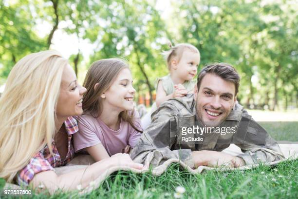 Soldier lying down on a blanket outdoors with his family