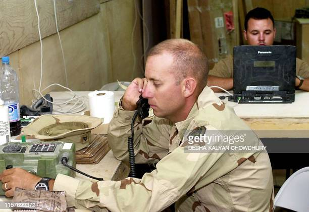 A US soldier makes a call from a military telephone while another checks email at Bagram Air Base 10 September 2002 Security and emotions were high...