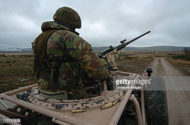 A soldier manning a .50 caliber heavy machine gun atop a Pink Panther Land Rover in Brecon, Wales.