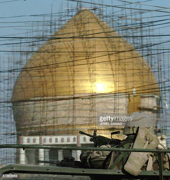 US soldier mans a machine gun mounted atop of a humvee as he patrols past the golden mosque of Imam Hassan alAskari in Samarra 02 October 2004 The...