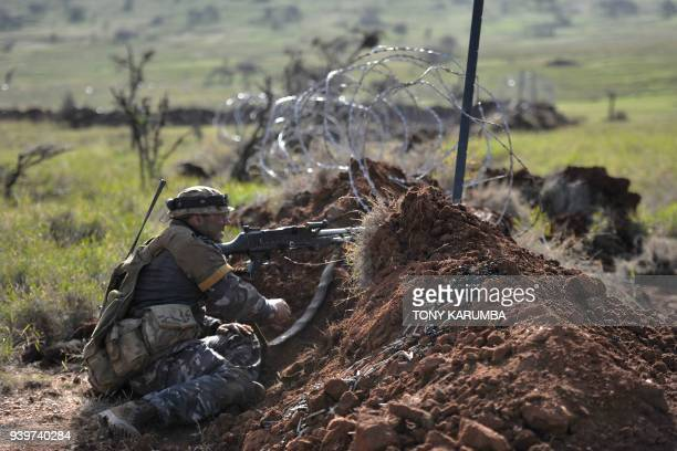 A soldier mans a machine gun position during a simulated military excercise of the British Army Training Unit in Kenya together with the Kenya...