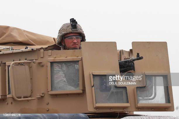 A US soldier mans an armoured vehicle part of a US army convoy patrolling near the city of Tall Tamr in the northwestern Syrian province of Hasakah...