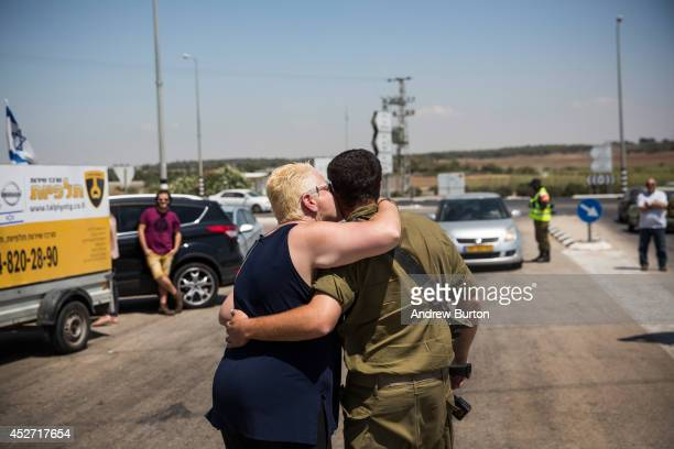 A soldier meets with his loved ones during a 12hour ceasefire just outside the militarized zone near the IsraeliGaza border on July 26 2014 near...