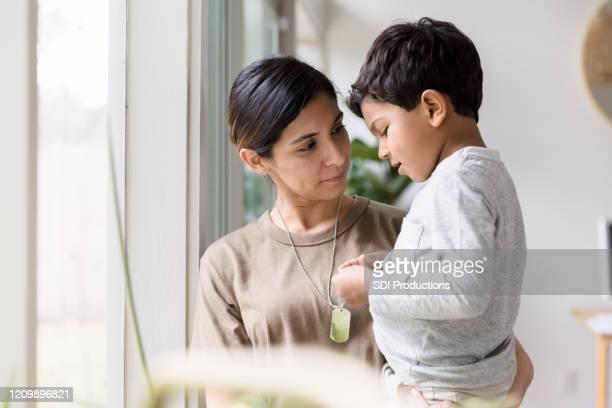 madre soldado escucha mientras el hijo pequeño habla sobre su despliegue - familia con un hijo fotografías e imágenes de stock