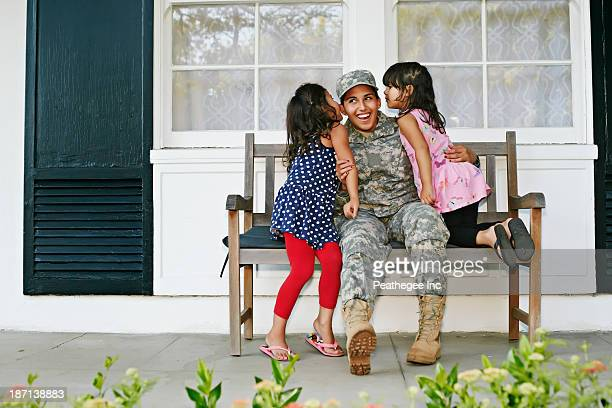 Soldier mother with daughters on patio