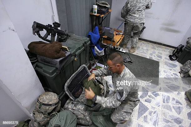 US soldier of Company C 2nd Battalion 5th Cavalry Regiment 1st Cavalry Division packs his bags as another sweeps the floor at their barracks at the...