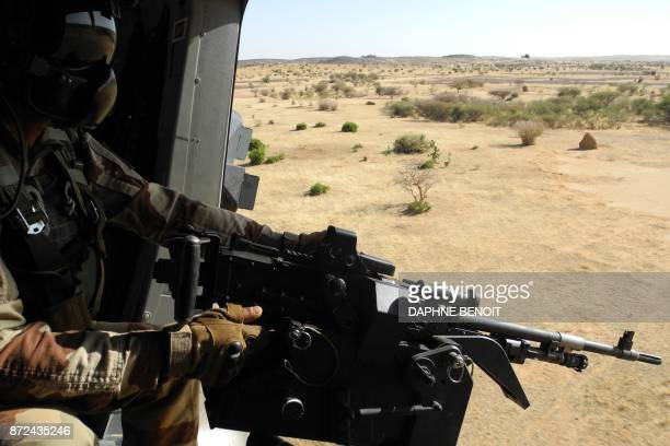A soldier of France's Barkhane mission holds a weapon as he patrols on November 1 2017 in central Mali in the border zone with Burkina Faso and Niger...