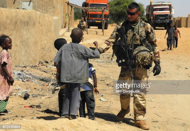 A soldier of France's Barkhane mission stands next to children as he patrols in InTillit on November 1 2017 in Mali as a joint antijihadist force...