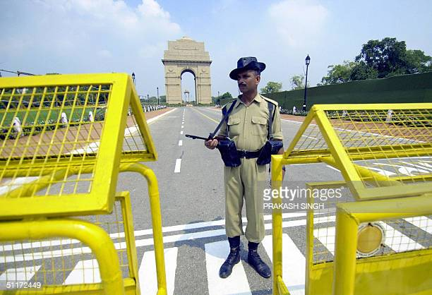 A soldier of India's Border Security Force's stands guard beside a barricade at India Gate as India celebrates its 57th anniversary of independence...