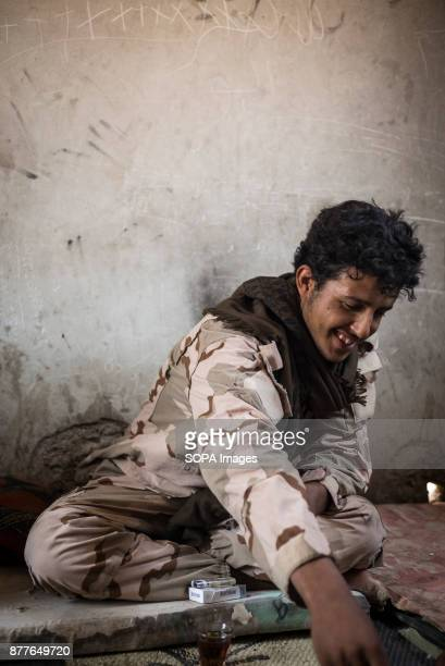 A soldier of Quwat Al Nukhba enjoy some tea and cigarette to get out of the summers heat of guarding an outpost Weathers get up to 50 degrees with...