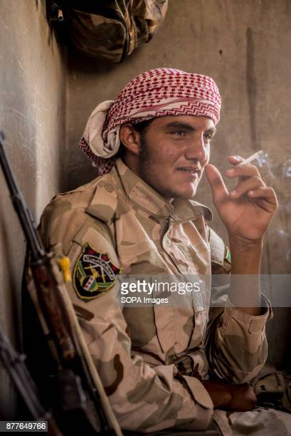 A soldier of Quwat Al Nukhba enjoy some tea and cigarette to get out of the summers heat of guarding an outpost Weather get up to 50 degrees with hot...