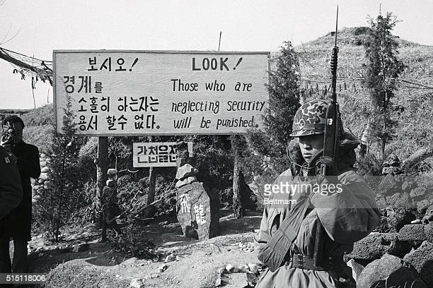 A soldier of South Korea's 25th Division stands guard at attention while a further warning in the form of a huge sign tells that this is a dangerous...