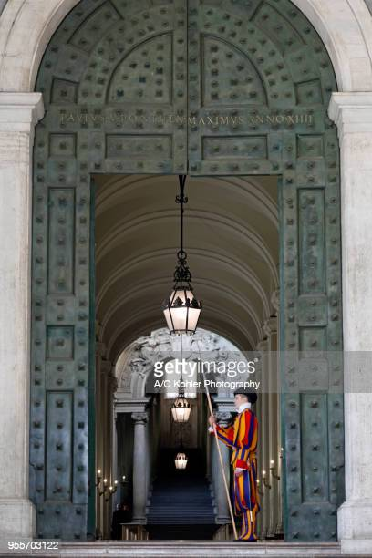 soldier of swiss guard guarding bronce door in the vatican, rome - vatikan stock-fotos und bilder