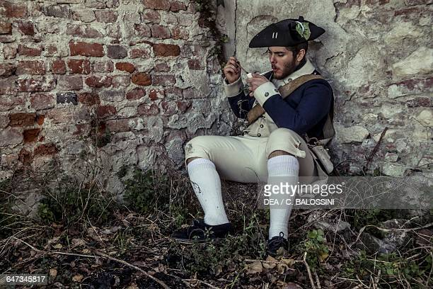 Soldier of the 4th Massachusetts Regiment wearing a tricorn hat blue uniform with a muzzleloading flintlock rifle lighting a pipe American...
