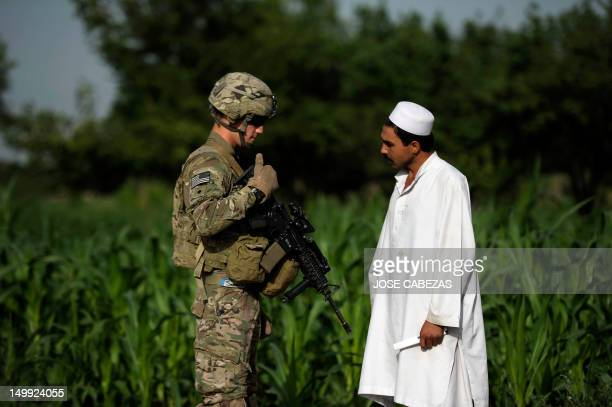 A US soldier of the 501st LABND Military Police Platoon speaks to a local Afghan resident in the village of Dzan Kila Buwri Tana district in Khost...