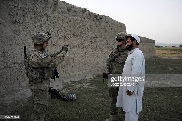 A US soldier of the 501st LABND Military Police Platoon takes a picture of a fellow soldier with a local resident during a patrol in the village of...