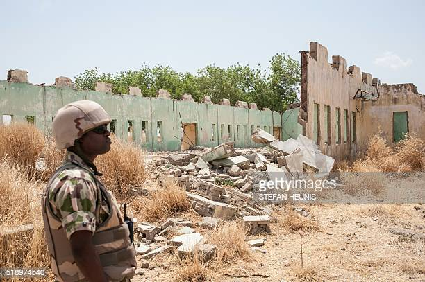 A soldier of the 7th Division of the Nigerian Army stands infront of the remaining dilapidated buildings of the Government Girls Secondary School...