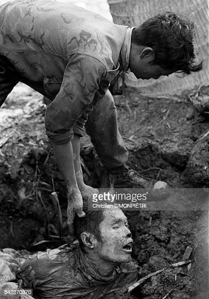 A soldier of the Army of the Republic of Vietnam handles a corpse