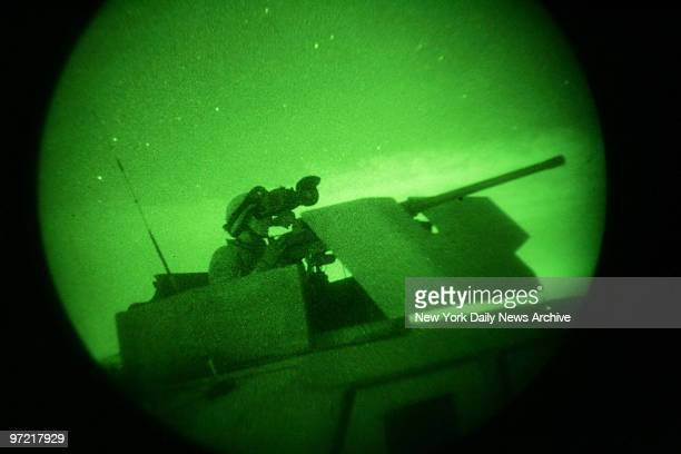 A soldier of the Army's 3rd Brigade 1st Infantry Division is seen through a night vision scope as he scans the horizon from a Humvee for possible...