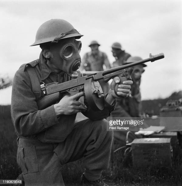 A soldier of the British Army training with a submachine gun in a gas mask during World War II UK June 1941